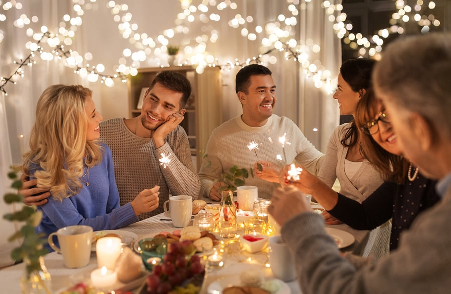 Friends and family gathered around a table during the holidays.