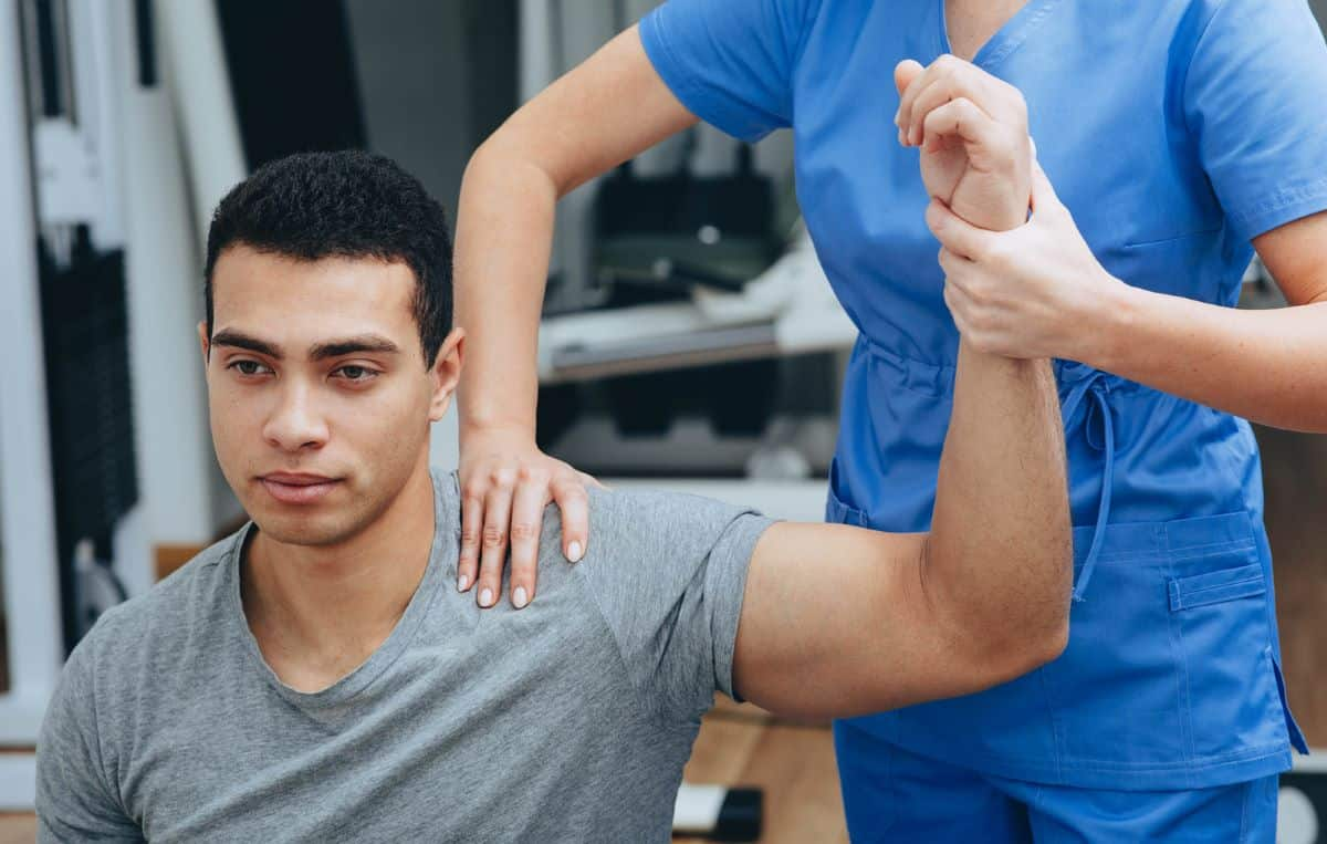 A professional athlete getting shoulder rehab from a physical therapist.
